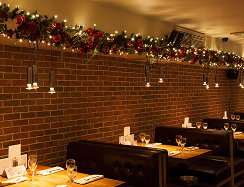 Restaurant with Christmas decorations hanging above seating area